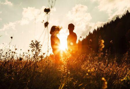 En amor, pareja, siluetas, entre, pasto alto, en, pradera puesta de sol