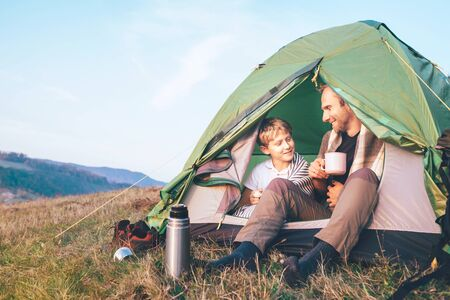 Father and son sit in camp tent drink hot tea and have conversation. Leisure time with father, parenthood