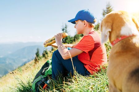 Little smiling boy weared baseball cap enjoying a huge baguette sandwich and his beagle dog friend watching it during a mountain hiking resting snack break time. 스톡 콘텐츠
