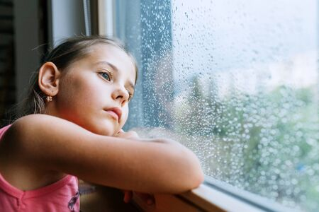 Little sad girl pensive looking through the window glass with a lot of raindrops. Sadness childhood concept image.