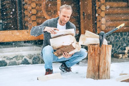 Man collecting chopped firewood on snowy yard for a house fireplace with heavy snowflakes background. Winter countryside holidays concept image Reklamní fotografie