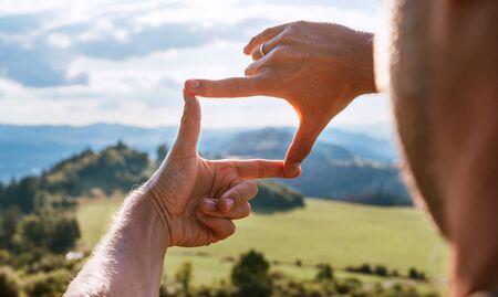 Rückansicht des Mannes, der die Berglandschaft mit den Fingern betrachtet und nach der besten Bildkomposition sucht, während er über die Bergkette wandert. Landschaftsfotograf oder Filmemacher Berufskonzept.