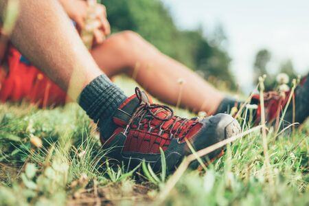 Backpackers trekking boots close up shot. Man has a rest break sitting on green grass and enjoying mountain walking, Active sports backpacking healthy lifestyle concept