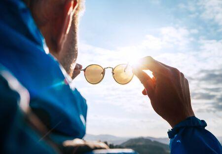 Backpacker man kijken naar felle zon door gepolariseerde zonnebril genieten van berglandschap.