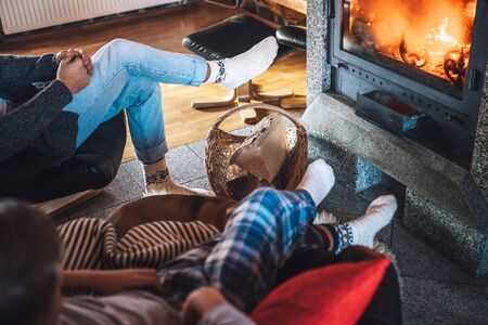 Father with son sitting in comfortable armchairs in their cozy country house near fireplace and enjoying a warm atmosphere and flame moves.