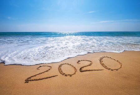 Feliz año nuevo 2020 se acerca el concepto de letras de la playa del océano tropical de arena.