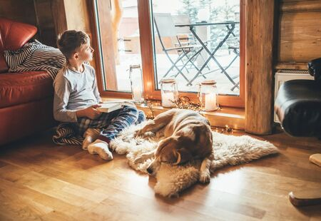 Boy reading book on the floor near slipping his beagle dog on sheepskin in cozy home atmosphere.