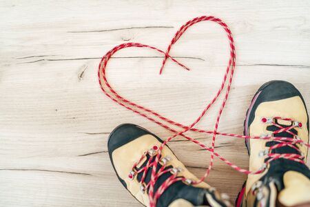 Conceptual image of the pair new trekking boots on the wooden floor  with released long shoelaces behind lying in heart shape. Stock Photo