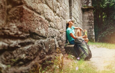 Tired female backpacker resting on the bench near the old antique brick wall castle on the famous Camino de Santiago way.