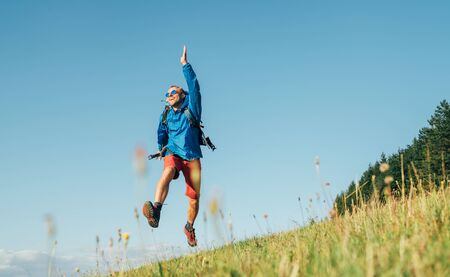 Backpacker traveler emotionally jumping over green grass mountain meadow with backpack with wide opened arms and legs.