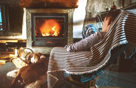 Boy sitting in comfortable armchair in cozy country house near fireplace and enjoying a warm atmosphere and flame moves. Фото со стока