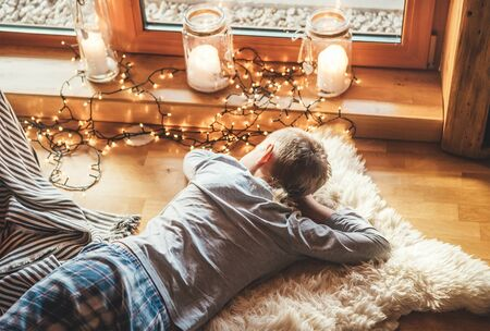 Boy lying on floor on sheepskin and looking in window in cozy home atmosphere.