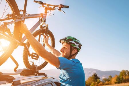 Mountain biker man take of his bike fronm the car roof. Active sport people concept image