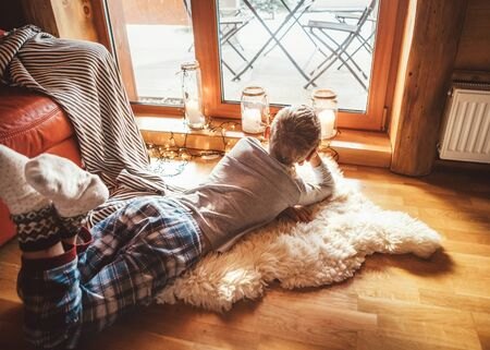 Boring boy lies on the floor and look sout from window in cozy and warm livivng room