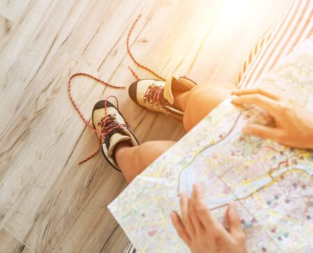 Young female inspecting a city map resting on the bed with untied trekking boots on wooden floor