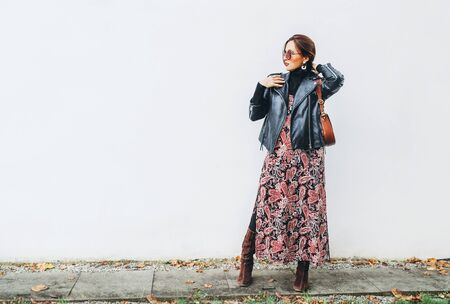 Smiling female dressed boho fashion style colorful long dress with black leather biker jacket with brown leather flap bag posing on the white wall