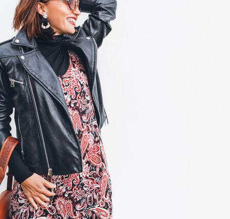 Smiling middle-aged female dressed boho fashion style colorful long dress with black leather biker jacket with brown leather flap bag posing on the white wall