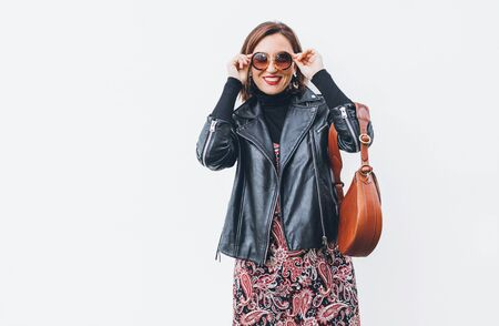 Smiling middle-aged female dressed boho fashion style colorful long dress with black leather biker jacket with brown leather flap bag putting on sunglasses posing on the white wall