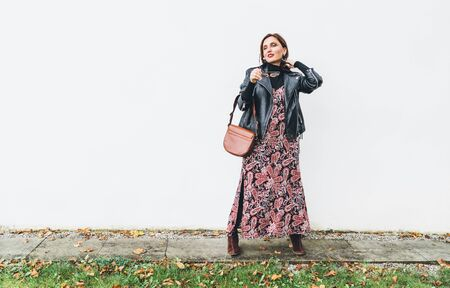 Smiling female dressed boho fashion style colorful long dress with black leather  jacket