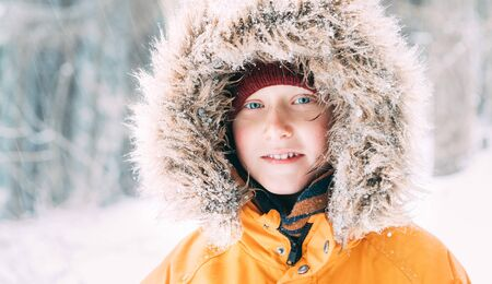 Boy dressed in Warm Hooded Casual Parka Jacket Outerwear walking in snowy forest cheerful smiling face portrait