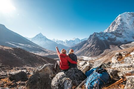 Couple having a rest on Everest Base Camp trekking route near Dughla 4620m. 版權商用圖片 - 134360827