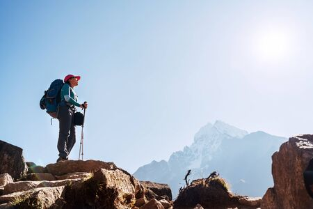 Young hiker backpacker female on cliff edge enjoying the Thamserku 6608m mountain during high altitude Acclimatization walk. Everest Base Camp trekking route, Nepal. Active vacations concept image