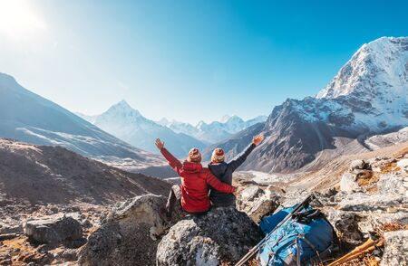 Couple rising arms rejoicing Everest Base Camp trekking route near Dughla 4620m.