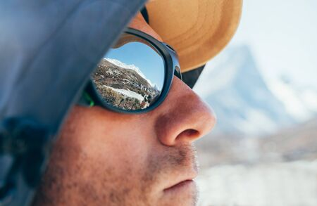 Portrait shot of high altitude unshaven happy mountain hiker in baseball cap and hood with snow peaks and mountain