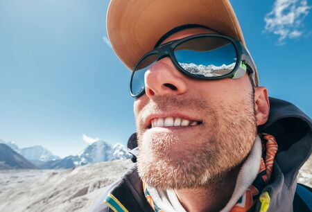 Ultra-wide lens angle portrait shot of high altitude mountain smiling unshaven happy hiker in baseball cap with snow peaks and mountain range beside him and reflected in mirror UV protected sunglasses