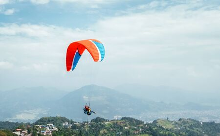 Paragliding with instructor using colorful paraglider over Pokhara town, Nepal. 스톡 콘텐츠 - 134361536