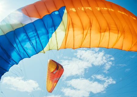 Colorful Paraglider waving on the wind with sunbeams optical flares with blu sky