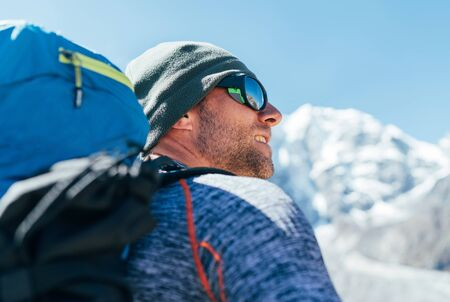 Portrait of unshaved Hiker man with backpack and UV protecting sunglasses on Taboche 6495m peakk background , He enjoying mountain views during Everest Base Camp trekking route.