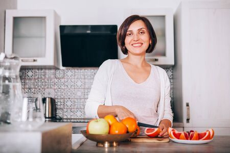 Beautiful young sincerely smiling female chopping grapefruit using a knife and cutting board in modern kitchen. Plenty of apples, grapefruits, kaki and oranges fruits, berries are on the tables.  Stock Photo