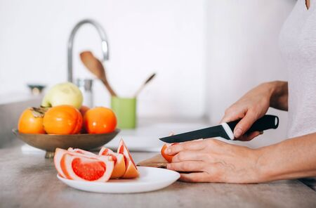 Young womans hands chopping grapefruit using a knife and cutting board in modern kitchen close up image. Plenty of apples, grapefruits, kaki and oranges fruits are on the plate.