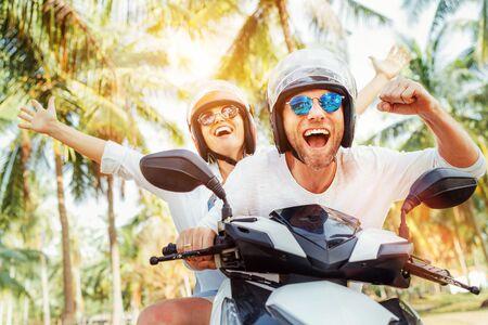 Glücklich lächelnde Paarreisende, die während des tropischen Urlaubs unter Palmen Motorradroller in Schutzhelmen fahren Standard-Bild