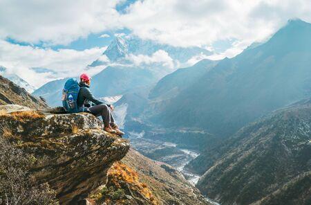 Young hiker backpacker female sitting on the cliff edge and enjoying Ama Dablam 6,812m peak view