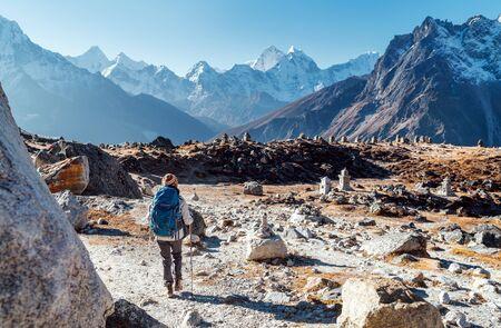 Giovane donna zaino in spalla che segue il percorso di trekking del campo base dell'Everest utilizzando bastoncini da trekking e godendo della vista sulla valle con il picco dell'Ama Dablam. È venuta all'Everest Memorial per Lost Mountaineers (4800m)
