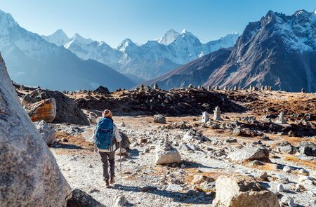 Young female backpacker following Everest Base Camp trekking route using trekking poles and enjoying valley view with Ama Dablam peak. She came to Everest Memorial to lost Mountaineers (4800m)
