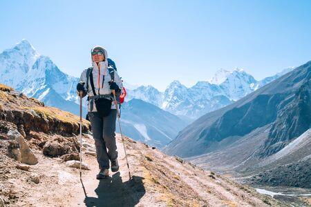 Jeune femme backpacker randonneur prenant une marche avec des bâtons de trekking pendant la route du camp de base de l'Everest en haute altitude près de Dingboche, Népal. Ama Dablam 6812m sur fond. Concept de vacances actives Banque d'images