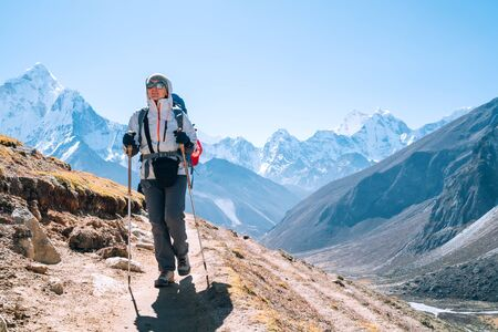 Young hiker backpacker female taking a walking with trekking poles during high altitude Everest Base Camp route near Dingboche,Nepal. Ama Dablam 6812m on background. Active vacations concept Stock Photo