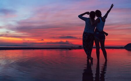 Two girlfriends hugging up and enjoying a rosepink sunset sky on the sea beach on the Samui Island,Thailand. Calm warm countries vacation concept image. 写真素材