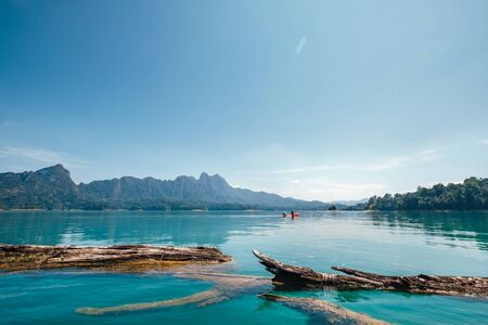 Old floating tree logs on the turquoise surface of eco lake in Thailand. Banque d'images