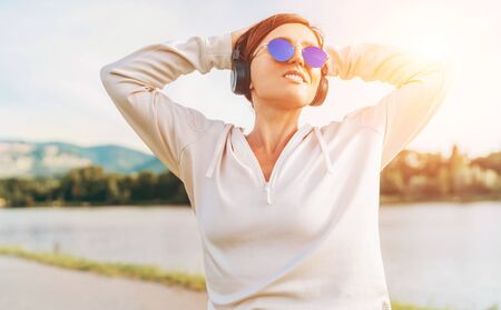 Young beautiful female in blue sunglasses listening to music using smartphone and wireless headphones cheerfully smiling. Walking with favorite music sounds concept image.