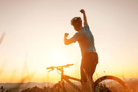 Man biker man meets a sunset in top of hill. He rising a one arm greeting on another successful day ending. Active sport people concept image
