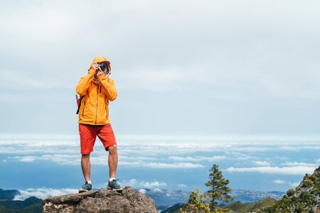 Young adult caucasian man dressed sporty clothes with backpack taking a picture from Pico Ruivo mount 1861m - the highest peak on the Madeira Island,Portugal. Active vacation concept image.