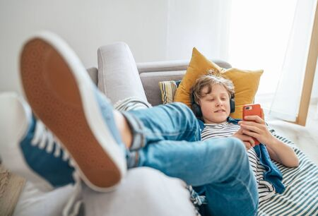 Preteen boy lying at home on cozy sofa dressed casual jeans and new sneakers listening to music and chatting Imagens