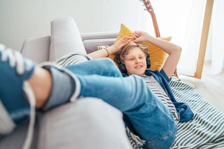 Smiling Preteen boy lying at home living room filled with sunlight on cozy sofa dressed casual jeans and sneakers listening to music Imagens