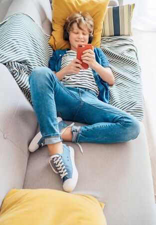 Preteen boy lying at home on cozy sofa dressed casual jeans and new sneakers listening to music