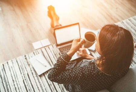 Businesswoman dressed in pajamas enjoying morning coffee on the floor office with laptop
