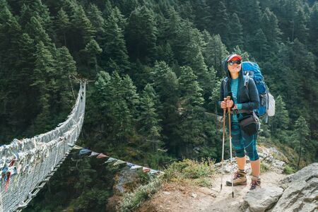 Young smiling female at canyon over Suspension Hillary Bridge with multicolored Tibetan Prayer flags Фото со стока